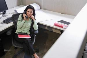 hispanische Frau am Telefon am Bürokabinenschreibtisch foto