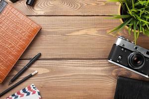 Schreibtisch Tisch mit Kamera, Zubehör und Blume foto
