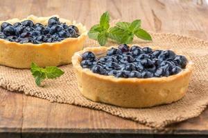 hausgemachte Torte mit frischen Blaubeeren auf einem Holzschreibtisch foto