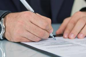 Geschäftsmann, der am Schreibtisch sitzt und einen Vertrag unterschreibt