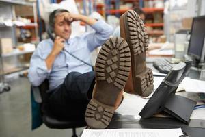Geschäftsmann, der Füße auf Schreibtisch im Lagerhaus aufstellt foto