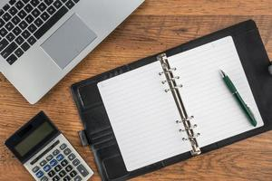 Notizbuch und Stift mit Taschenrechner auf dem Schreibtisch