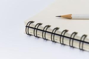 weißer Bleistift mit leerem Notizbuch foto