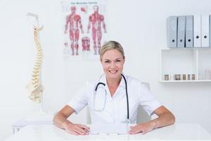 Arzt sitzt an ihrem Schreibtisch