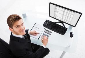 Geschäftsmann, der Ausgaben am Schreibtisch berechnet foto