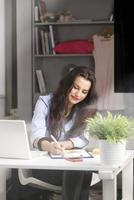 junge schöne Geschäftsfrau, die am Schreibtisch arbeitet foto