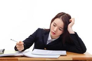 junger asiatischer Student, der Probleme auf Schreibtisch hat. foto