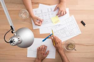 vier Hände arbeiten an einem Schreibtisch foto