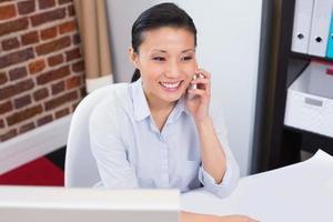 lächelnde Führungskraft mit Handy am Schreibtisch foto