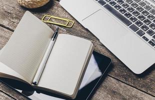 Notizbuch und Laptop auf altem Holzschreibtisch foto
