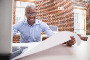 Gelegenheitsgeschäftsmann, der seinen Laptop am Schreibtisch benutzt
