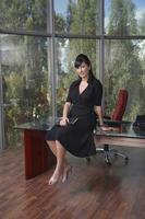 junge Geschäftsfrau, die auf Schreibtisch im Büro sitzt foto