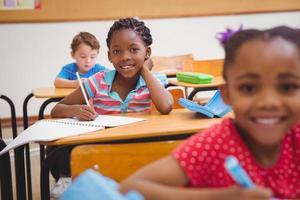 süße Schüler schreiben am Schreibtisch im Klassenzimmer