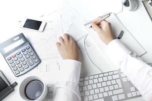 Börsenmakler, der am Schreibtisch arbeitet und auf Notizblock schreibt