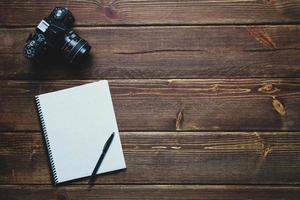 Notebook und Vintage-Kamera auf dem Schreibtisch foto