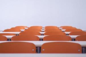 leeres Klassenzimmer mit orangefarbenen Tischen und Stühlen foto