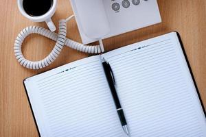 Kundendiensttisch mit Kaffee, Notizen und Stift foto