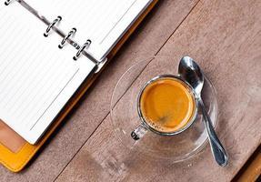 leere Notizbuch-Kaffeetasse auf hölzernem Hintergrund foto