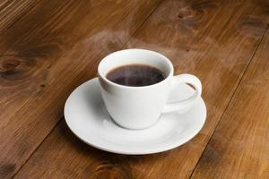 weiße Tasse dampfenden Kaffees auf Holztisch foto