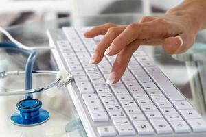 Arzt oder Krankenschwester, die Tastatur mit Stethoskop tippt