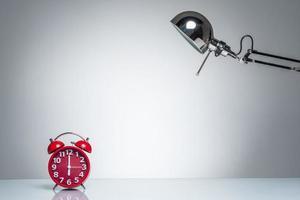 roter Wecker mit Schreibtischlampe aufleuchten foto