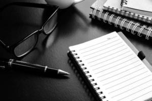 Tasse Kaffee mit Notizbuch auf Schreibtisch, Arbeitsplatz foto