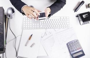 Frau, die am Schreibtisch arbeitet und auf Smartphone tippt foto