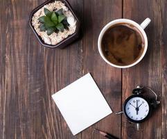 Kaffee, Sukkulente, Stück Papier und Wecker foto