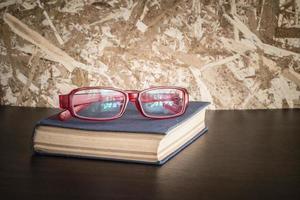 Brille und Buch mit Filtereffekt im Retro-Vintage-Stil