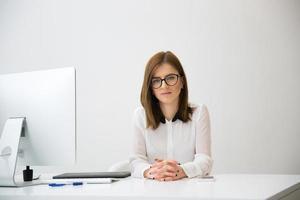 Geschäftsfrau sitzt am Tisch im Büro foto