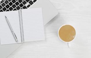 Laptop mit Kaffee und leerem Notizblock auf weißem Desktop foto