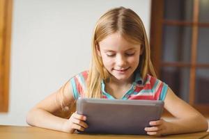 süßer Schüler in der Klasse mit Tablet-PC foto