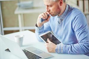 Mann sitzt an einem Computertisch mit einem Tablet und einem Smartphone foto