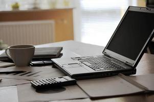 Arbeitsplatz - offener Laptop mit schwarzem Bildschirm und Geschäftsdokumenten foto
