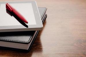 Tablet-Gerät auf Notebook am Holztisch foto