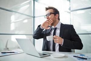 Geschäftsmann mit Kaffee, der an einem Laptop arbeitet, gähnt sichtbar