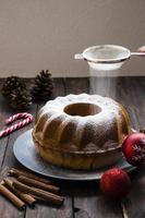 Streuen von Zucker auf Weihnachtskuchen auf hölzernem Hintergrund foto