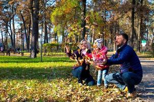 sorglose europäische Familie, die im Herbstpark spielt foto