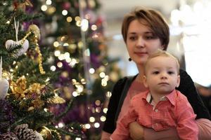 Familie posiert am Weihnachtsbaum foto