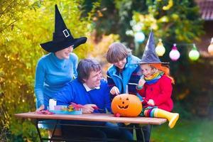 Familie schnitzt Kürbis an Halloween foto