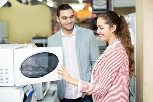 glückliches Familienpaar, das neue Mikrowelle wählt foto