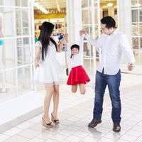 glückliche Familie, die im Einkaufszentrum spielt foto