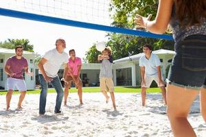 männliche Mehrgenerationenfamilie, die Volleyball im Garten spielt