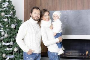 Familienporträt in der Nähe des Weihnachtsbaumes. foto