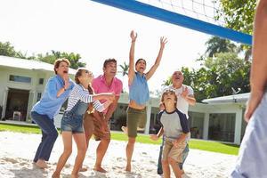 Mehrgenerationenfamilie, die Volleyball im Garten spielt