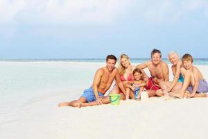 Familie mit mehreren Generationen, die Spaß am Strandurlaub hat