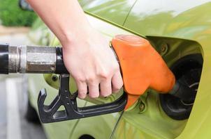 Frauen halten die Tankdüse zum Auto an der Tankstelle