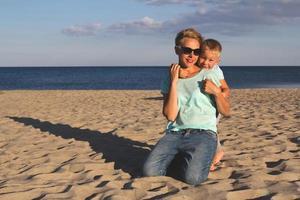 glückliche Familie, die im Sommer am Strand ruht foto