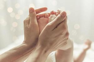 Mutter berührt die Füße des Neugeborenen foto