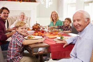 Familie mit Großeltern, die Thanksgiving-Mahlzeit am Tisch genießen foto